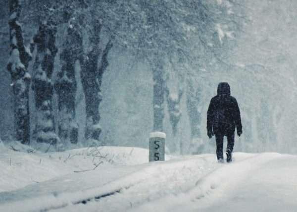 Mann spaziert auf Schienen im Schnee